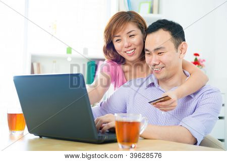 Happy Asian couple shopping online with credit card and computer at home