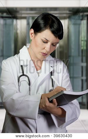 Thinking medical doctor with stethoscope. Over hospital background
