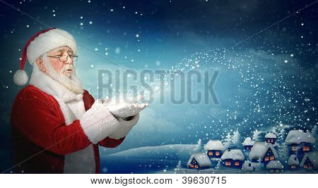 Santa Claus blowing snow to blue  little town at night