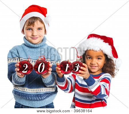 Kids in Santa's hat holding a christmas ball