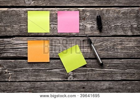 Color sticky note paper sheets fountain pen. Closeup on old wooden table.
