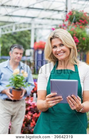 Cheerful florist holding a tablet pc in garden center with customer standing behing holding flower pot
