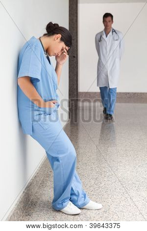 Sad nurse leans against wall in hospital corridor with doctor approaching