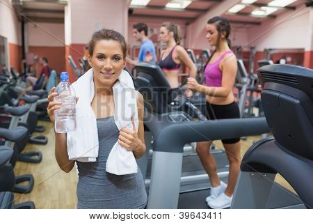 Happy woman drinking water in gym after exercise
