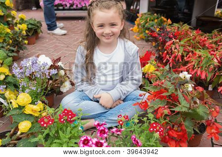 Little girl sitting on path surrounded by flowers in garden center