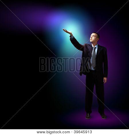 Joven empresario de éxito, con una luz brillante en su mano como símbolo de éxito y advancem