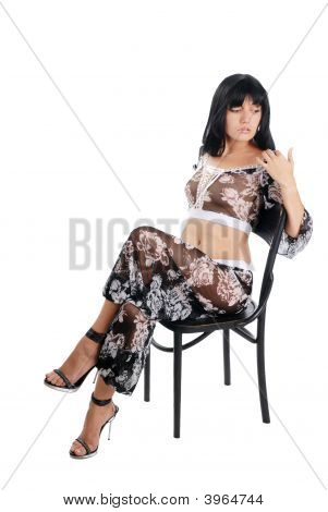 Model In Black Suit Sitting On Chair, Isolated On White