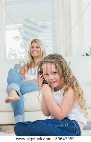 Daughter using mobile phone while her mother laughing on the sofa