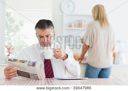 Mann sitzt am Küchentisch beim Lesen einer Zeitung und hält eine Tasse Kaffee vor der Arbeit