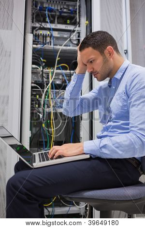 Data technician getting stressed over servers with laptop