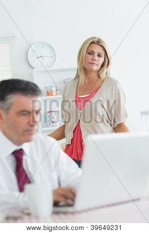 Wife looking upset at husband using laptop in kitchen at breakfast