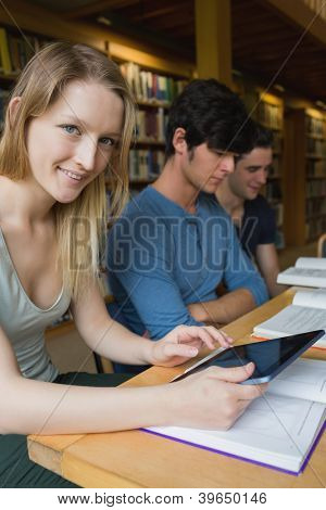 Woman holding a tablet pc sitting at the library and smiling