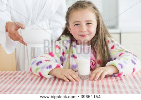 Happy little girl with glass of milk getting cereal from her mother at breakfast in kitchen