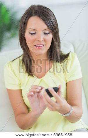 smiling woman touching her smartphone in the living room