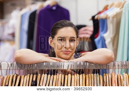 Woman  leanig on a clothes rack in a shop
