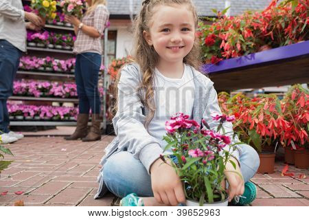 Little girl holding flowers while smiling sitting on path of garden center