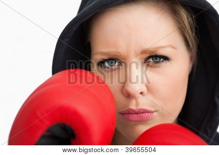 Woman protecting her face with boxing gloves against white background