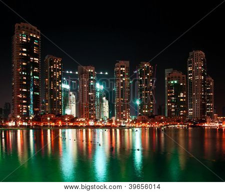nice view of dubai city at night with reflections in water
