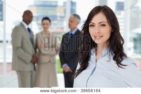 Young executive smiling and standing in a bright room with her team behind her