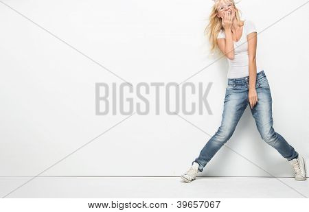 Young cheerful lady over empty white board