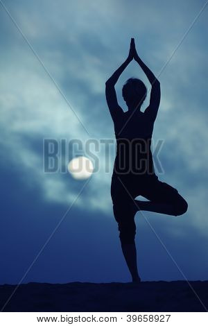 Woman in yoga Tree pose over blue night sky background