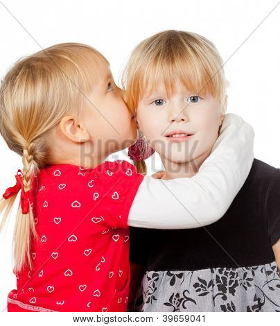 Portrait of little girl  telling a secret to her friend over a white background
