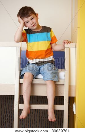 Sleepy little boy sitting on bunk bed.