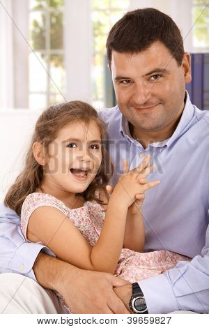 Portrait of father and little daughter hugging, smiling, looking at camera.