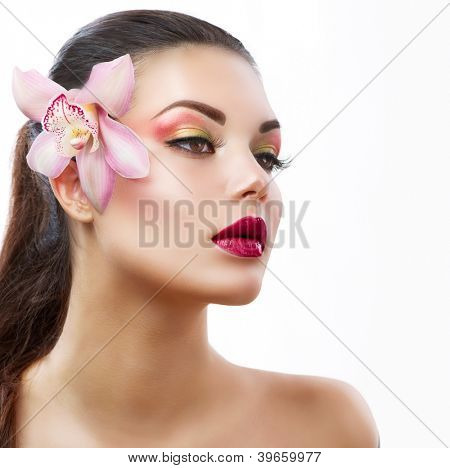 Beauty Woman With Orchid Flower.Beautiful Model Woman Face.Perfect Skin. Professional Make-up.Makeup.Isolated on a White Background.Fashion