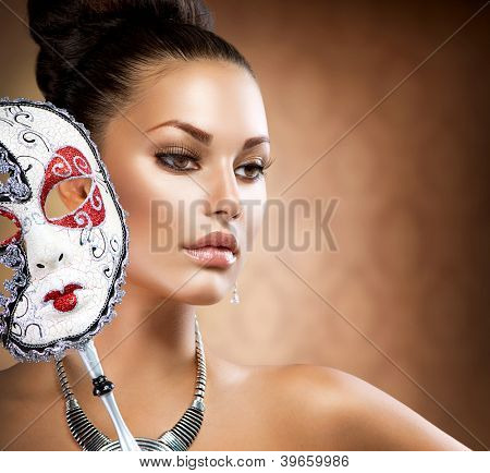 Beauty Model Girl with Carnival Mask.Masquerade Woman.Holiday Dress and Makeup. Fashion Brunette Portrait
