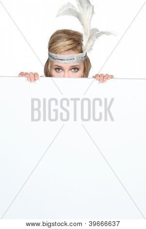Woman wearing a feathery headpiece hiding behind a blank sign