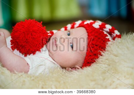 newborn girl lying in  red hat