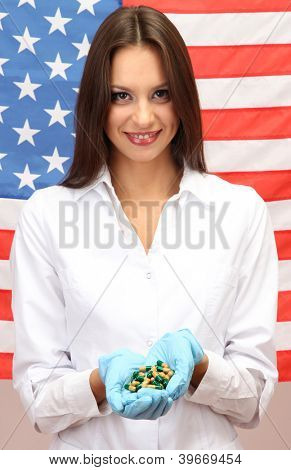 Portrait of female doctor or scientist showing and analyzing pills over American Flag background
