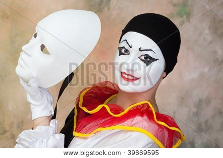 Female smiling pierrot holding a serious white face mask