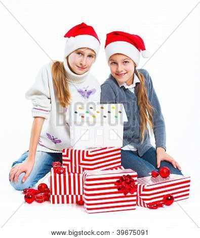 Happy girls in Santa's hat with gift box