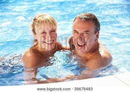 Senior Couple Having Fun In Swimming Pool