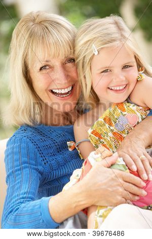 Grandmother And Granddaughter Relaxing On Sofa Together