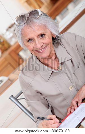 Elderly lady paying bills