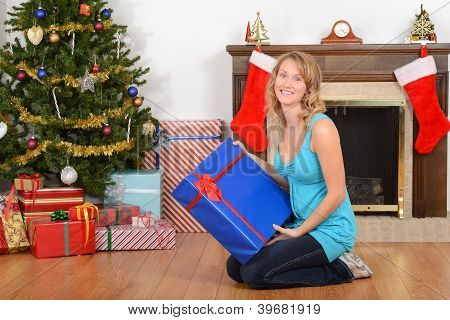 Young woman with blue christmas present
