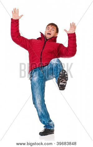 Full length portrait of a young man dressed with winter clothes slipping on floor isolated on white background