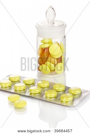Pills packed in blister and receptacle isolated on white