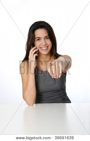 Brunette girl with smartphone pointing arm towards camera