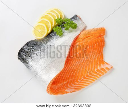 fresh salmon fillet with skin, decorated with sliced lemon and parsley