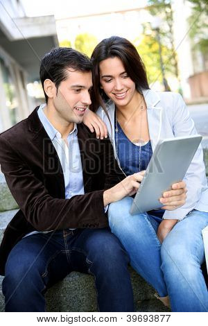 Young couple websurfing on internet with tablet in town