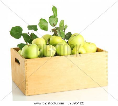 juicy apples with green leaves in wooden crate, isolated on white