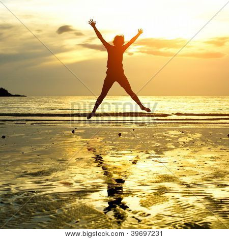 Silhouette of young girl, jumping against of sea sunset