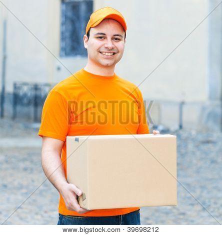 Portrait of an handsome deliverer holding a box
