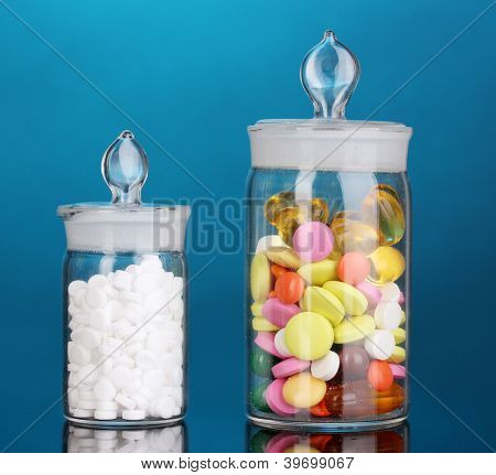 Capsules and pills in receptacles on blue background