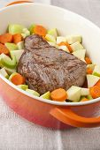 stock photo of dutch oven  - Beef Roast prepared with carrots apples and celery in french oven - JPG