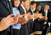 stock photo of business success  - business team clapping in an office facing the camera - JPG